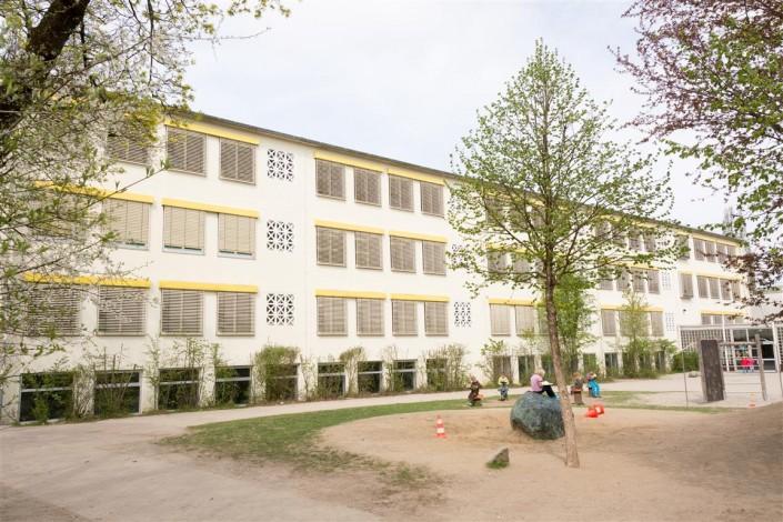 Bild: Lesende Kinder sitzen im Schulhof